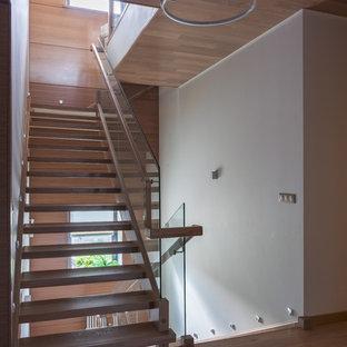 Свежая идея для дизайна: п-образная лестница в современном стиле с деревянными ступенями и стеклянными перилами без подступенок - отличное фото интерьера