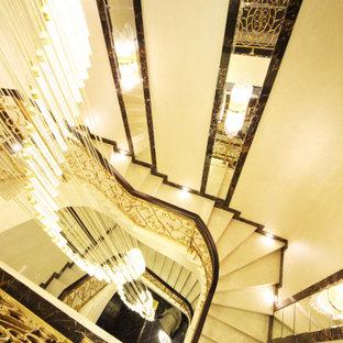 Imagen de escalera en U y papel pintado, ecléctica, grande, con escalones de mármol, contrahuellas de mármol, barandilla de metal y papel pintado