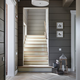 На фото: угловая лестница среднего размера в современном стиле с крашенными деревянными ступенями, стеклянными подступенками и деревянными перилами