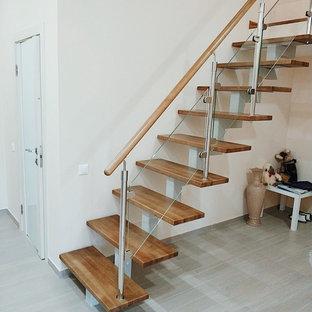 エカテリンブルクの中サイズの木のコンテンポラリースタイルのおしゃれな直階段 (金属の蹴込み板、木材の手すり) の写真