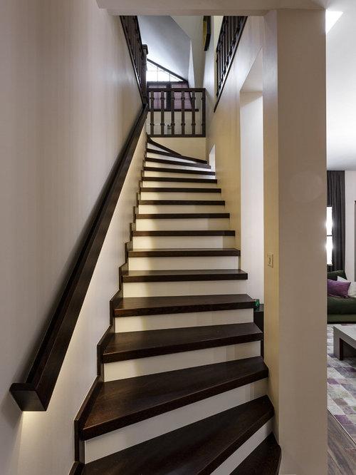 На фото: изогнутые лестницы в классическом стиле с деревянными ступенями и деревянными перилами
