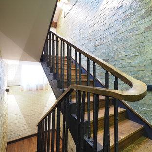 モスクワの中サイズの木のインダストリアルスタイルのおしゃれな折り返し階段 (木の蹴込み板、金属の手すり) の写真