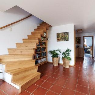 На фото: изогнутая лестница в современном стиле с деревянными ступенями и деревянными подступенками с