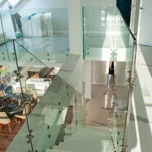 Ispirazione per una piccola scala a rampa dritta con pedata in marmo e parapetto in vetro