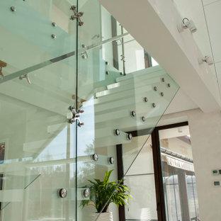 Esempio di una piccola scala a rampa dritta con pedata in marmo e parapetto in vetro