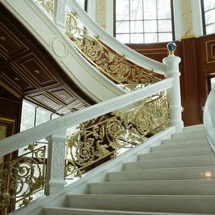 Immagine di una scala classica con pedata in marmo, alzata in marmo e parapetto in metallo