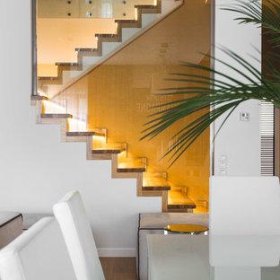Стильный дизайн: п-образная лестница в современном стиле с деревянными ступенями, деревянными подступенками и стеклянными перилами - последний тренд