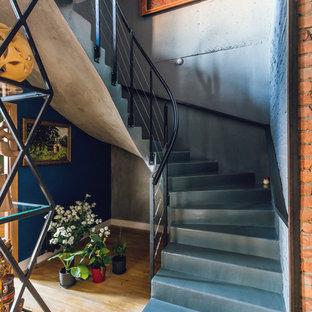 На фото: изогнутая лестница в стиле лофт с бетонными ступенями, бетонными подступенками и металлическими перилами с