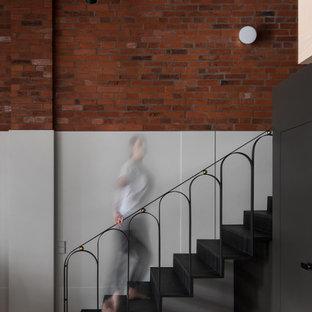 Ejemplo de escalera en L y panelado, minimalista, de tamaño medio, con escalones de metal, contrahuellas de metal, barandilla de metal y panelado