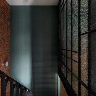 Foto de escalera en L y ladrillo, minimalista, de tamaño medio, con escalones de metal, contrahuellas de metal, barandilla de metal y ladrillo