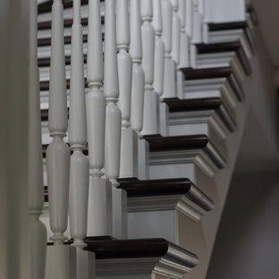 モスクワの広いコンクリートのトラディショナルスタイルのおしゃれな折り返し階段 (木の蹴込み板、木材の手すり) の写真