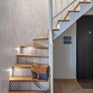 Ejemplo de escalera curva, actual, con escalones de madera, contrahuellas con baldosas y/o azulejos y barandilla de metal