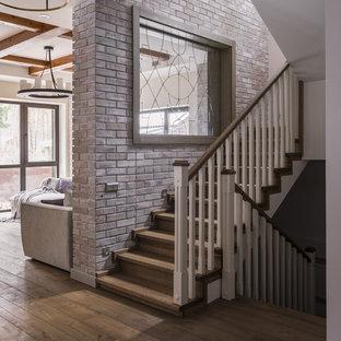 На фото: большая п-образная лестница в стиле современная классика с деревянными ступенями, деревянными подступенками и деревянными перилами с