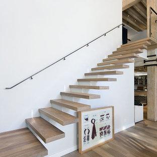 Пример оригинального дизайна: лестница на больцах в стиле лофт с деревянными ступенями и металлическими перилами без подступенок