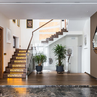 Mid-sized trendy concrete u-shaped glass railing staircase photo in Saint Petersburg with marble risers
