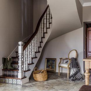 Пример оригинального дизайна интерьера: изогнутая лестница в стиле современная классика с деревянными ступенями, подступенками из плитки и деревянными перилами