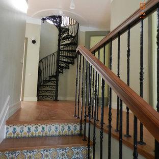 Diseño de escalera de caracol, de tamaño medio, con escalones de metal, contrahuellas con baldosas y/o azulejos y barandilla de metal