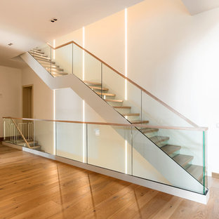 Inspiration for a large contemporary painted straight wood railing staircase remodel in Moscow with glass risers