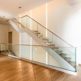 モスクワの大きいフローリングのコンテンポラリースタイルのおしゃれな直階段 (ガラスの蹴込み板、木材の手すり) の写真