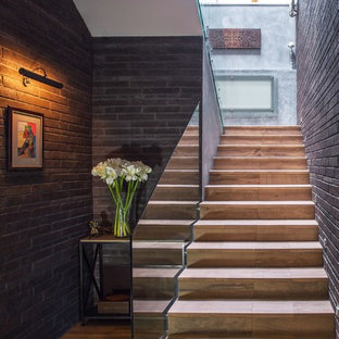 Foto de escalera en U, actual, con escalones con baldosas, contrahuellas con baldosas y/o azulejos y barandilla de vidrio