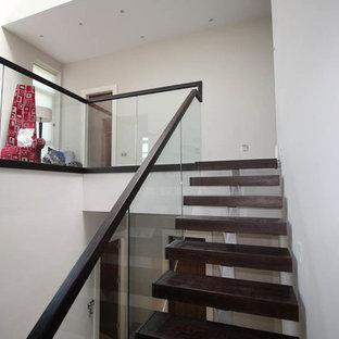 Immagine di una scala a rampa dritta nordica di medie dimensioni con pedata in legno e parapetto in vetro