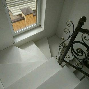 Ejemplo de escalera en U, clásica, grande, con escalones de acrílico y barandilla de metal