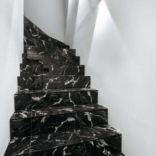 Неиссякаемый источник вдохновения для домашнего уюта: изогнутая лестница в современном стиле с мраморными ступенями и подступенками из мрамора