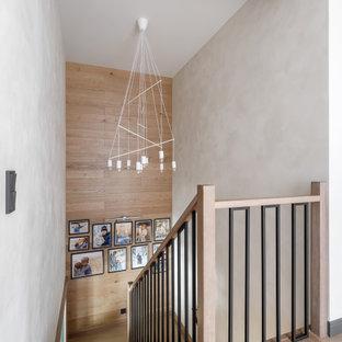 Mittelgroße Rustikale Holztreppe in U-Form mit gefliesten Setzstufen, Holzgeländer und Holzdielenwänden in Sankt Petersburg