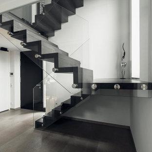На фото: лестница в современном стиле с стеклянными перилами