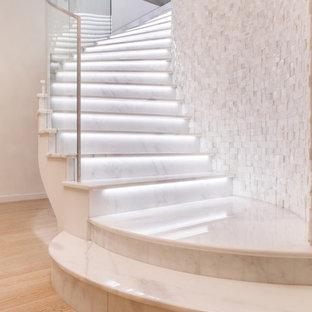 Идея дизайна: изогнутая лестница в современном стиле с мраморными ступенями, подступенками из мрамора и стеклянными перилами
