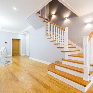 Diseño de escalera en U, clásica renovada, de tamaño medio, con escalones de madera, contrahuellas de hormigón y barandilla de madera