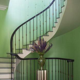 На фото: изогнутая лестница в современном стиле с крашенными деревянными ступенями