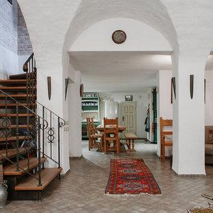 На фото: изогнутая лестница в средиземноморском стиле с деревянными ступенями и металлическими перилами без подступенок с