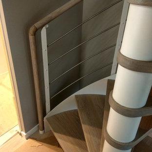 Ejemplo de escalera de caracol, clásica renovada, pequeña, con escalones de madera y barandilla de metal