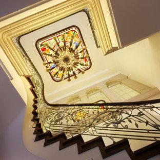 Ejemplo de escalera en U y panelado, tradicional renovada, grande, con escalones de madera, contrahuellas de madera, barandilla de metal y panelado