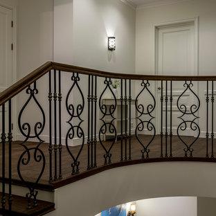 Diseño de escalera en L, tradicional renovada, de tamaño medio, con escalones de madera pintada, contrahuellas de madera y barandilla de varios materiales