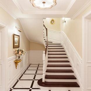 На фото: изогнутая лестница в стиле современная классика с деревянными ступенями и деревянными перилами с