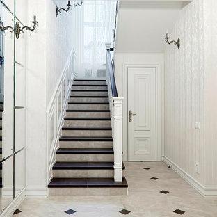 モスクワの中サイズのタイルのトラディショナルスタイルのおしゃれな折り返し階段 (タイルの蹴込み板、木材の手すり) の写真
