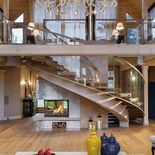 Неиссякаемый источник вдохновения для домашнего уюта: изогнутая лестница в стиле рустика с деревянными ступенями без подступенок