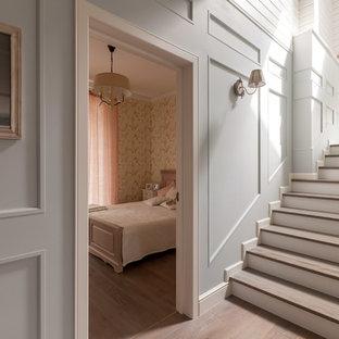 На фото: п-образная лестница среднего размера в стиле современная классика с крашенными деревянными ступенями, деревянными подступенками и деревянными перилами