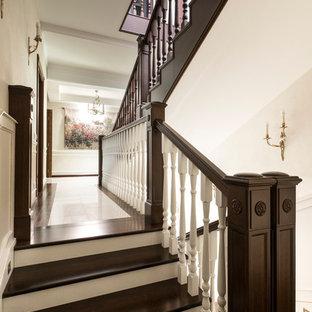 Новые идеи обустройства дома: п-образная лестница в классическом стиле с деревянными ступенями, деревянными перилами и крашенными деревянными подступенками