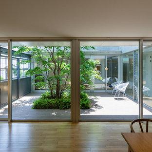 Exemple d'un salon asiatique avec un mur blanc et un sol en bois clair.