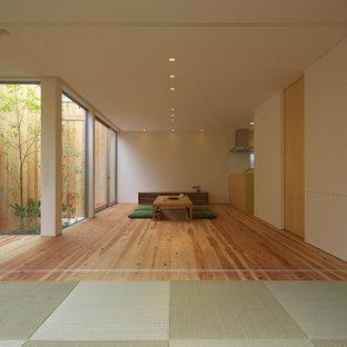 Exempel på ett mellanstort asiatiskt vardagsrum, med vita väggar, tatamigolv, en väggmonterad TV och grönt golv