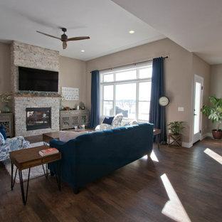 Cette photo montre un grand salon ouvert avec une salle de réception, un mur beige, un sol en vinyl, une cheminée standard, un manteau de cheminée en pierre de parement, un téléviseur fixé au mur et un sol marron.