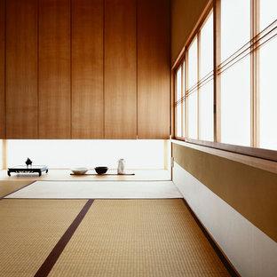 Cette image montre un salon asiatique avec un mur marron, aucune cheminée, un sol de tatami, aucun téléviseur et un sol beige.