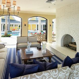 ボストンのトロピカルスタイルのおしゃれなリビング (黄色い壁、両方向型暖炉、レンガの暖炉まわり) の写真