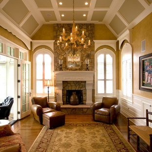 Expansive traditional formal enclosed living room in Boston with brown walls, medium hardwood floors, a hanging fireplace, a stone fireplace surround, no tv and brown floor.