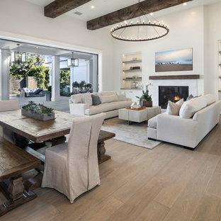 Ejemplo de salón abierto, tradicional renovado, con paredes blancas, suelo de madera en tonos medios, chimenea tradicional y suelo marrón