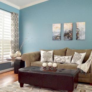 Ispirazione per un piccolo soggiorno minimalista aperto con libreria, pareti blu, pavimento in legno massello medio, nessun camino, cornice del camino in cemento e nessuna TV