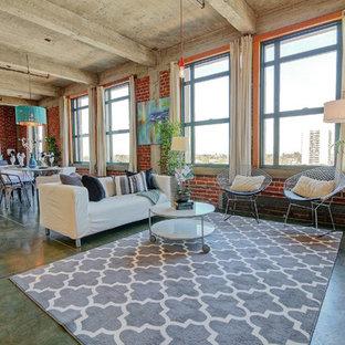 Immagine di un grande soggiorno industriale aperto con pareti rosse e pavimento in cemento